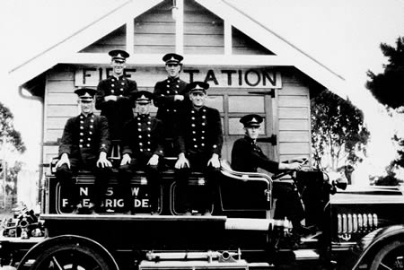 A black and white photo of fire fighters siting on a fire truck outside of their fire station.